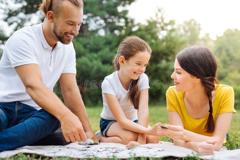 Lycklig familj som gör pusslet på picknick royaltyfri bild