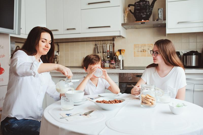 Lycklig familj som har frukosten hemma Moder med två ungar som äter i morgonen i modernt vitt kök arkivbild