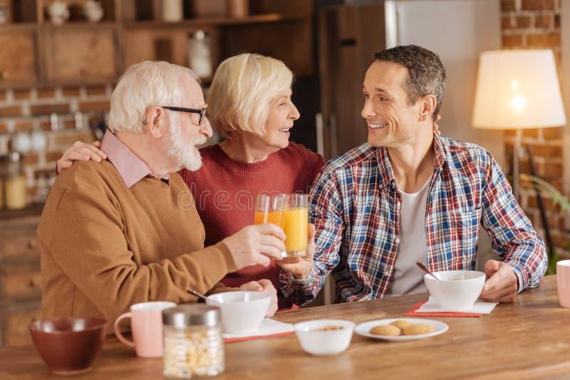 Lycklig familj som har frukosten i köket royaltyfri foto