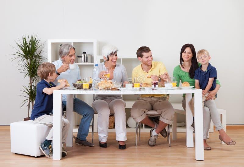 Lycklig familj som har frukosten tillsammans arkivfoto