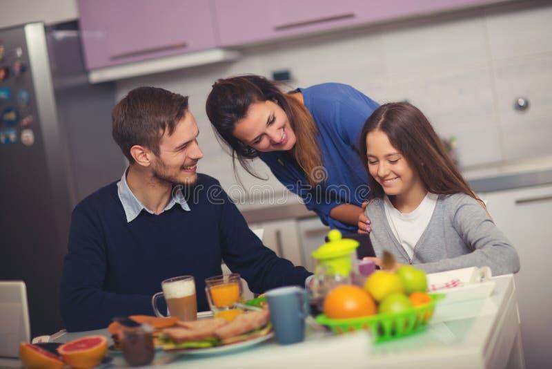 Lycklig familj som har frukosten tillsammans hemma arkivbild