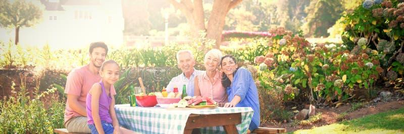 Lycklig familj som har grillfesten i parkera arkivfoton