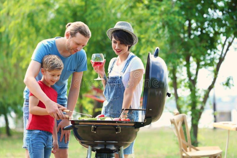 Lycklig familj som har grillfesten med det moderna gallret royaltyfri bild