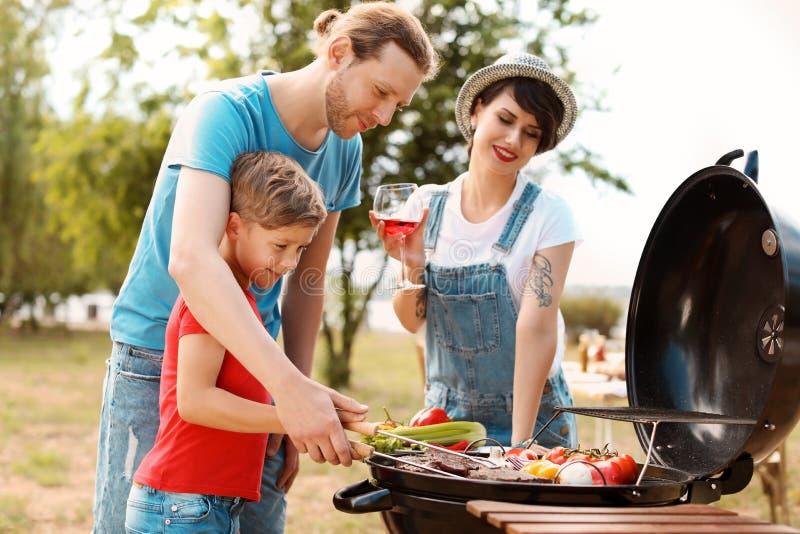 Lycklig familj som har grillfesten med det moderna gallret royaltyfri foto