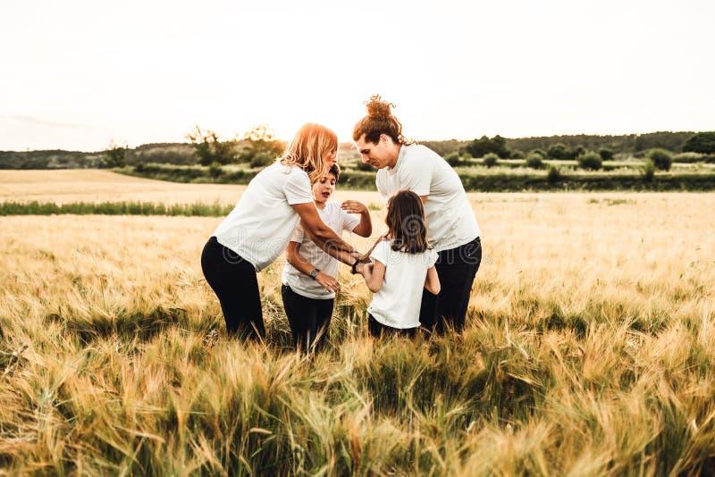 Lycklig familj som har gyckel i f?ltet Begrepp av en glad och enig familj arkivbild