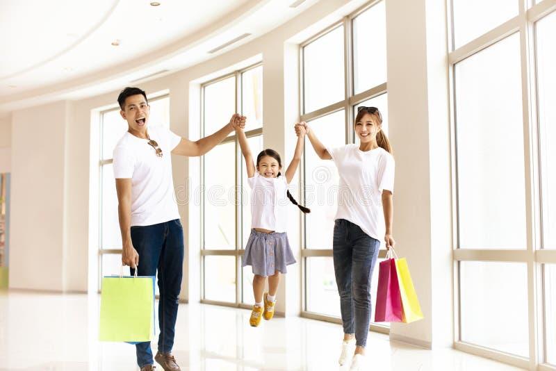 Lycklig familj som har gyckel i shoppinggallerian royaltyfria bilder