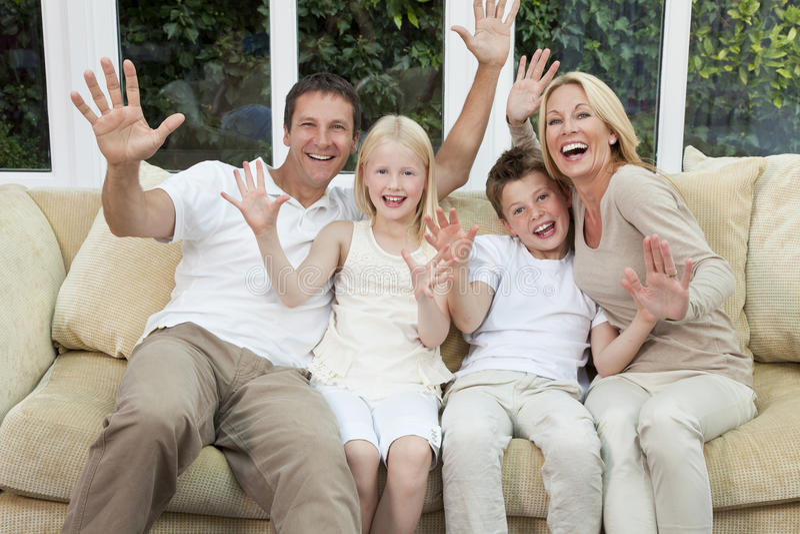 Lycklig familj som har gyckel sitta hemma arkivfoto