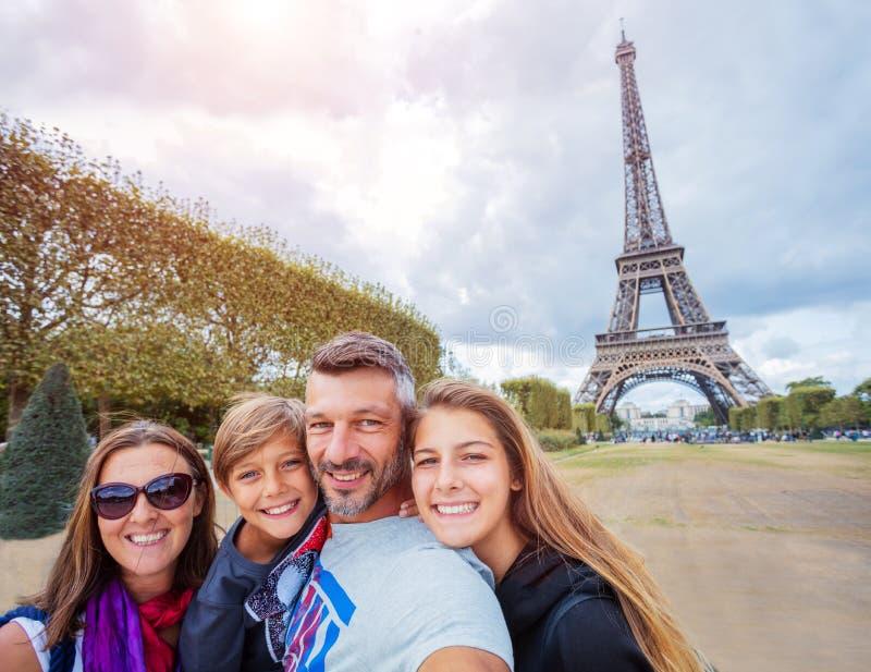 Lycklig familj som har gyckel tillsammans i Paris nära Eiffeltorn royaltyfri fotografi