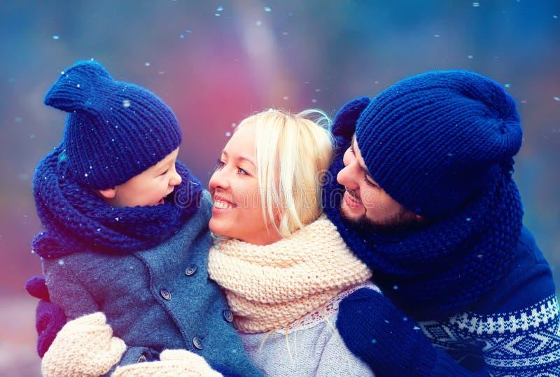 Lycklig familj som har gyckel tillsammans under vintersnö royaltyfria foton
