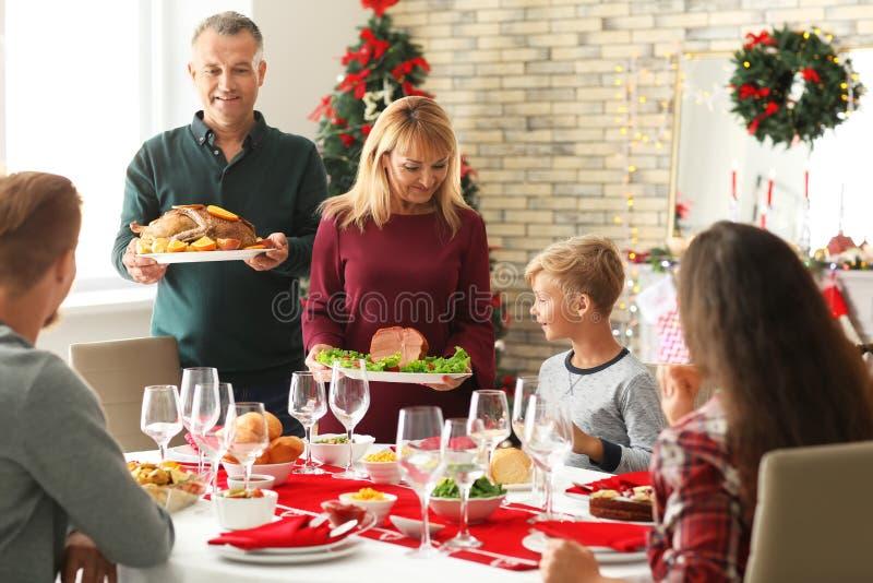 Lycklig familj som har julmatst?llen hemma arkivbilder