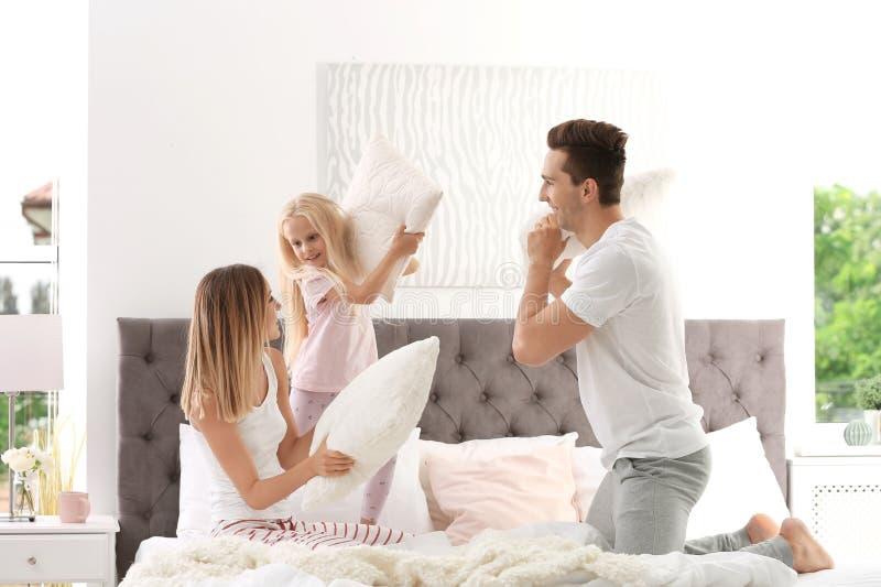 Lycklig familj som har kuddekamp på säng royaltyfria foton