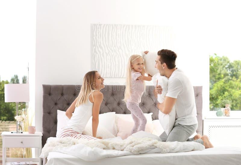 Lycklig familj som har kuddekamp på säng arkivbild