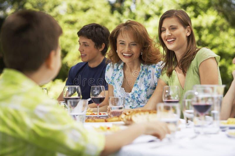 Lycklig familj som har lunch i trädgård royaltyfri bild