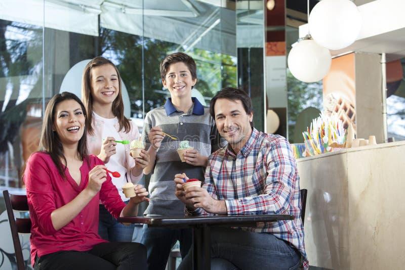 Lycklig familj som har olika glassar i mottagningsrum arkivbild