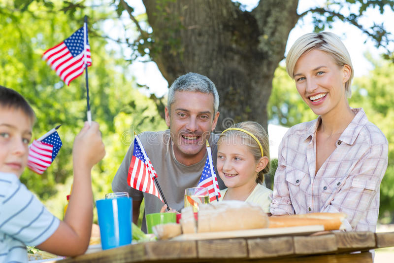 Lycklig familj som har picknick- och innehavamerikanska flaggan royaltyfri foto