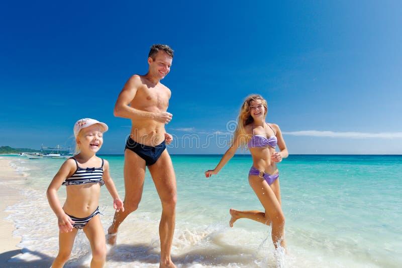 Lycklig familj som har rolig spring på en tropisk sandig strand arkivfoton