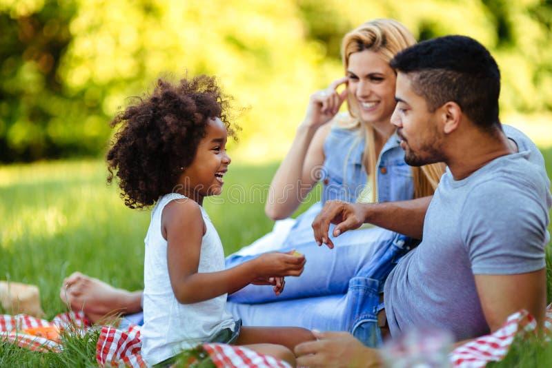 Lycklig familj som har rolig tid på picknick royaltyfri fotografi