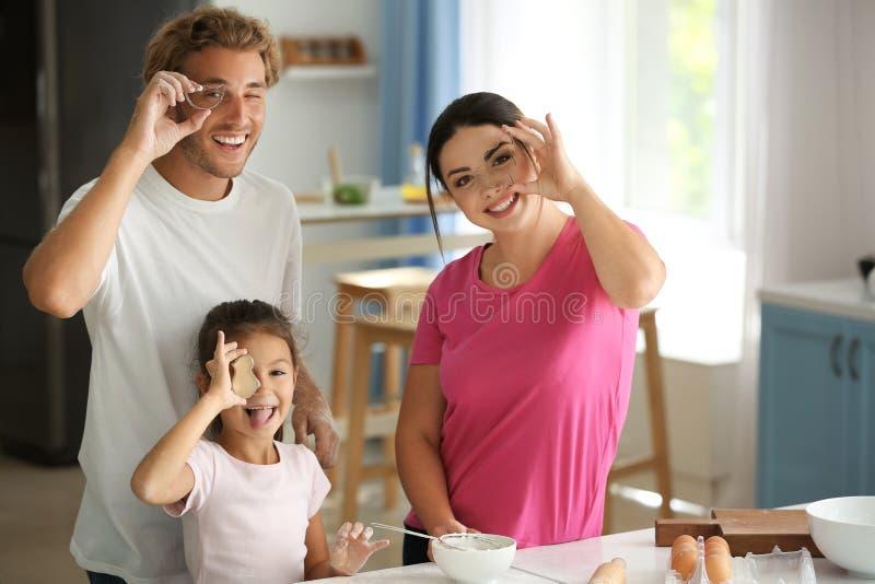 Lycklig familj som har roligt, medan laga mat i kök arkivbild