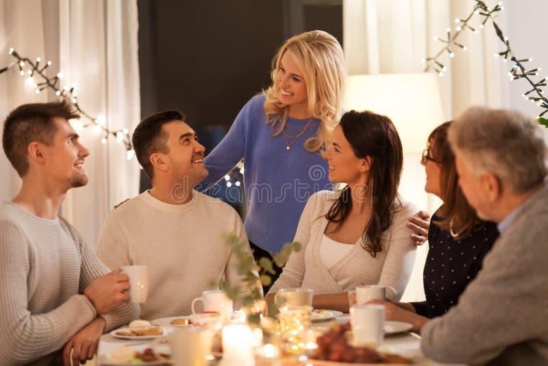 Lycklig familj som har tebjudningen hemma arkivfoton