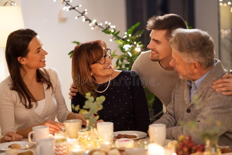 Lycklig familj som har tebjudningen hemma arkivbild