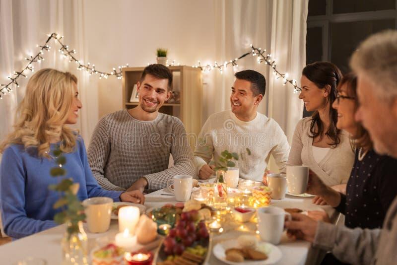Lycklig familj som har tebjudningen hemma royaltyfria bilder