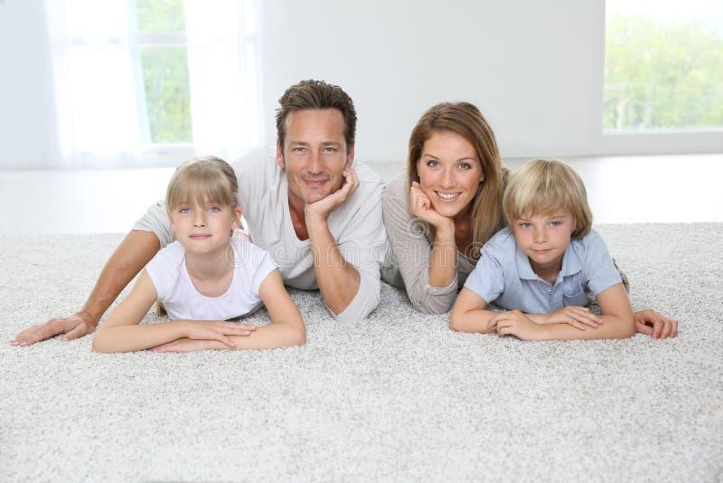 Lycklig familj som hemma ligger på matta royaltyfri foto
