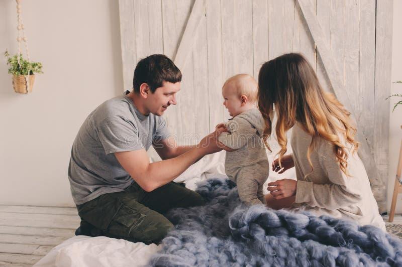 Lycklig familj som hemma spelar på sängen Livsstiltillfångatagandet av modern, fader och behandla som ett barn arkivbilder