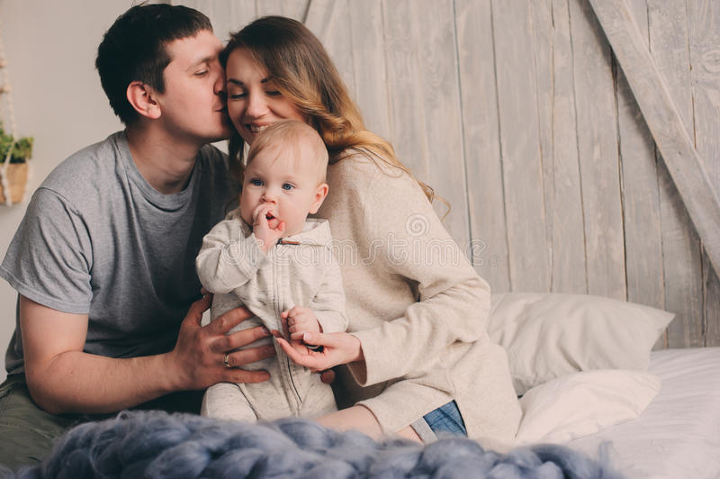 Lycklig familj som hemma spelar på sängen Livsstiltillfångatagandet av modern, fader och behandla som ett barn arkivbild