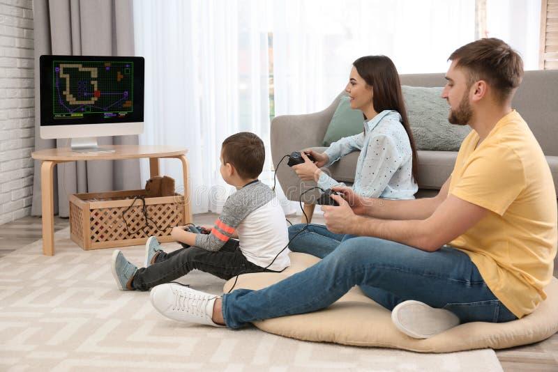 Lycklig familj som hemma spelar videospel royaltyfri fotografi