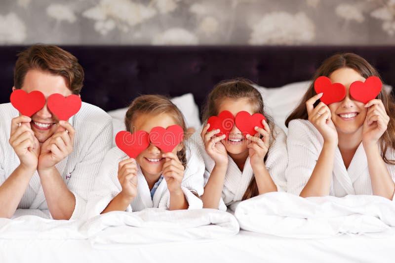 Lycklig familj som kopplar av i hotellrum royaltyfri fotografi