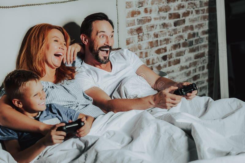 Lycklig familj som lägger i säng- och leklekar royaltyfri foto