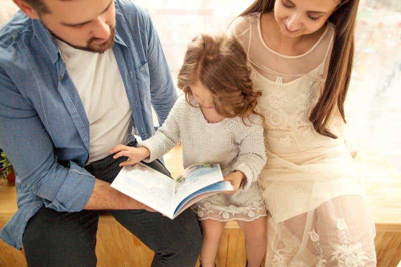 lycklig familj som läser en bok till hennes dotter arkivbilder