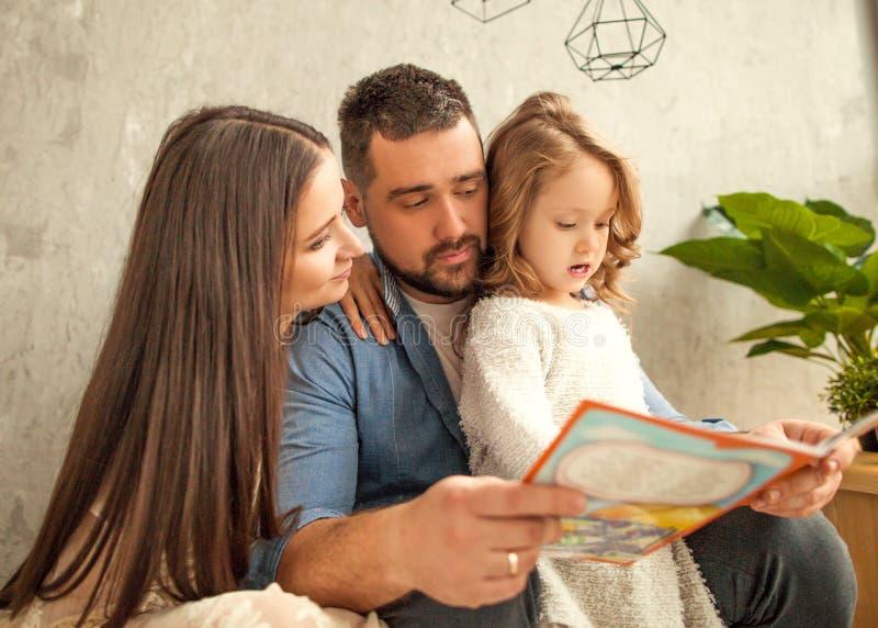 lycklig familj som läser en bok till hennes dotter dagblomman ger mödrar mumsonen till royaltyfri foto