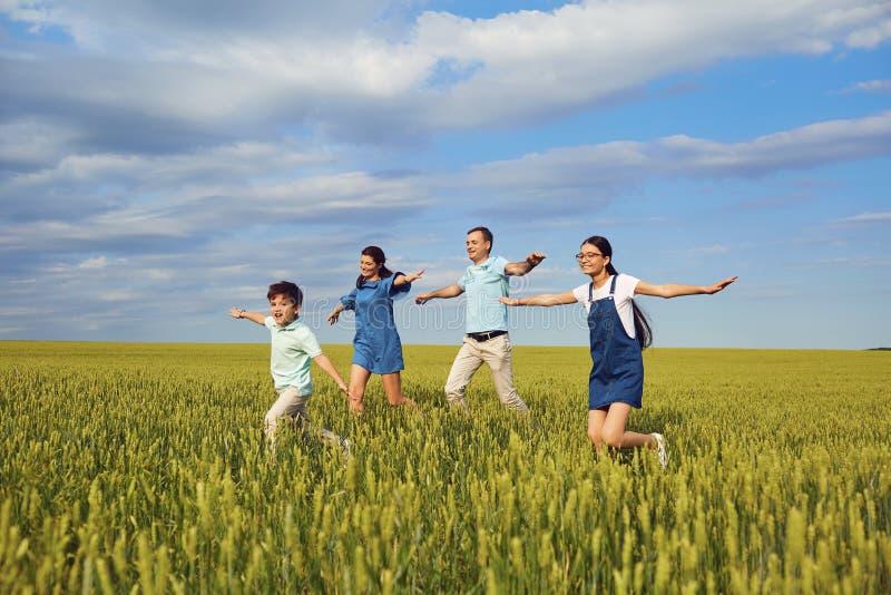 Lycklig familj som ler att köra på fältet i natur arkivfoto