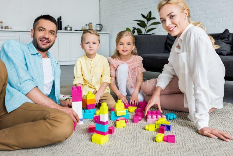 lycklig familj som ler på kameran, medan spela med färgrika kvarter arkivbild