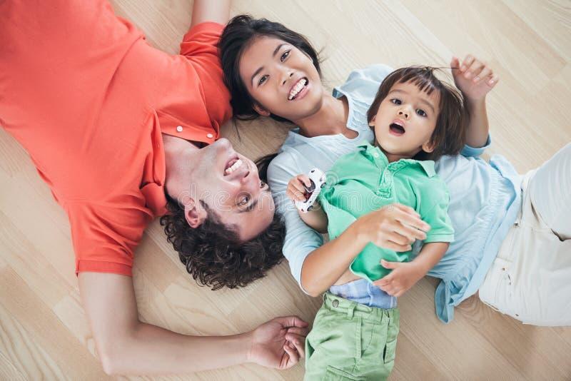 Lycklig familj som ligger på golv arkivfoto