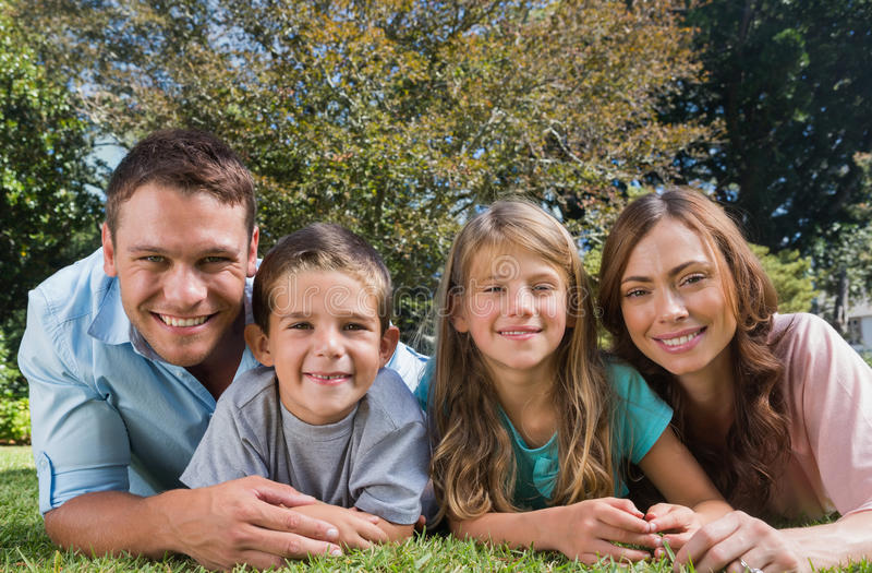 Lycklig familj som ligger på gräset royaltyfria bilder