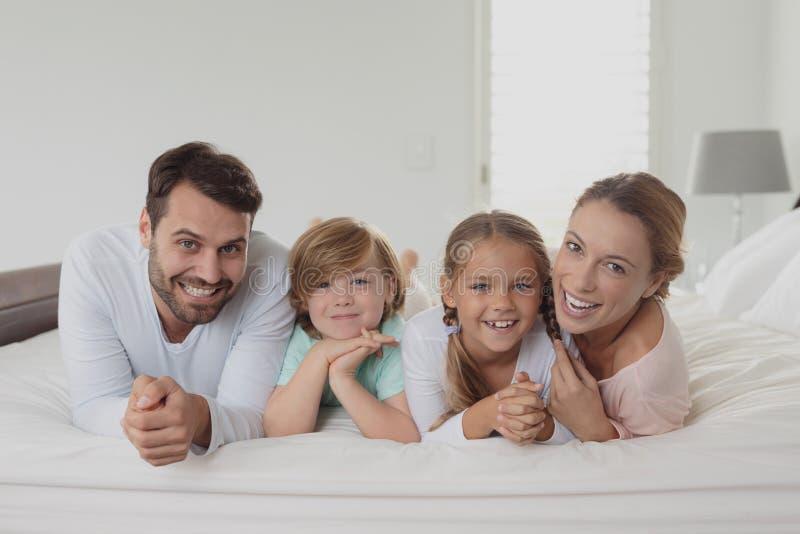 Lycklig familj som ligger på säng och ser kameran royaltyfri fotografi