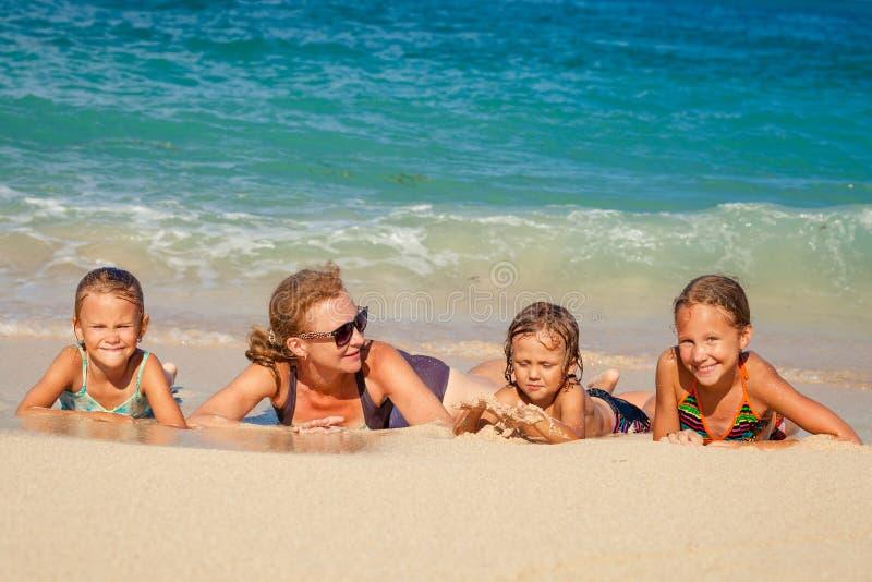 Lycklig familj som ligger på stranden fotografering för bildbyråer