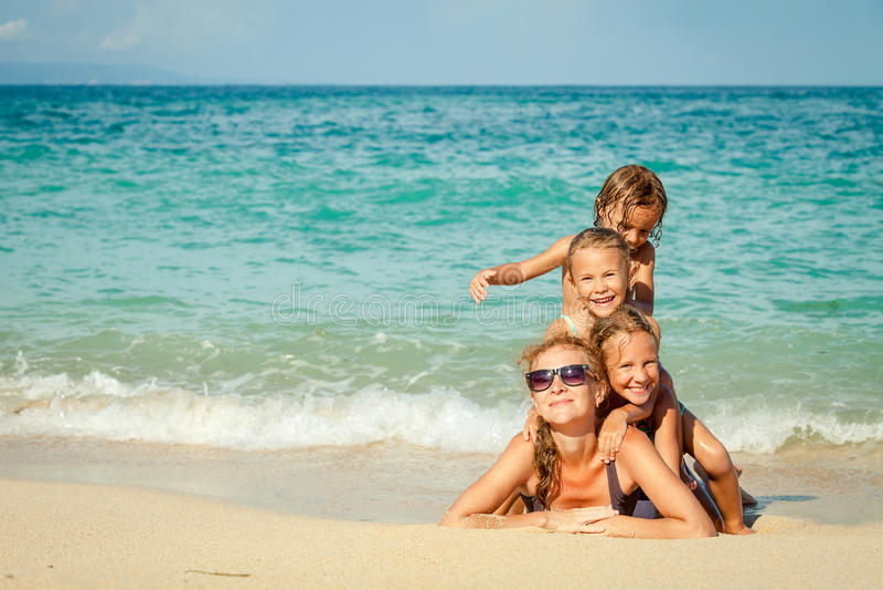 Lycklig familj som ligger på stranden royaltyfri bild