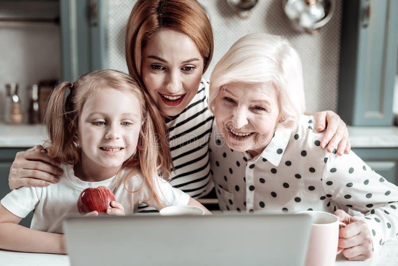 Lycklig familj som lutar till bärbara datorn och ler, medan meddela med släktingar arkivbilder