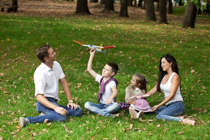 Lycklig familj som ner ligger i trädgården royaltyfria foton