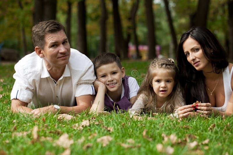 Lycklig familj som ner ligger i trädgården royaltyfri foto