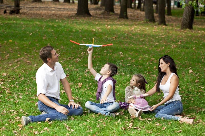 Lycklig familj som ner ligger i trädgården arkivbild