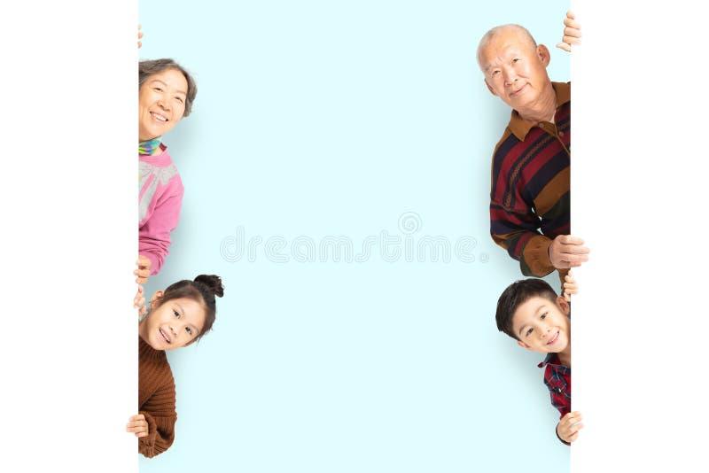 Lycklig familj som poserar bak tomt vitt bräde arkivbilder
