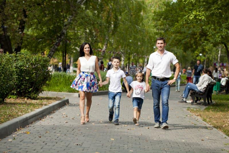 Lycklig familj som promenerar den förorts- gatan royaltyfri foto