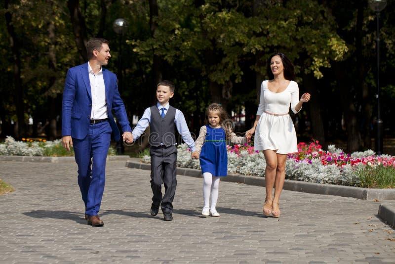 Lycklig familj som promenerar den förorts- gatan arkivfoto