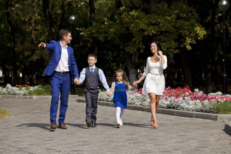 Lycklig familj som promenerar den förorts- gatan fotografering för bildbyråer