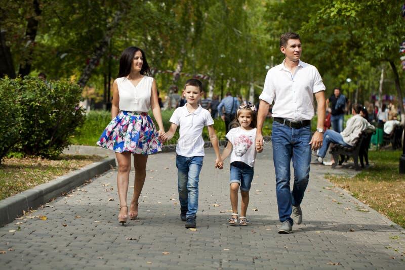 Lycklig familj som promenerar den förorts- gatan royaltyfria bilder