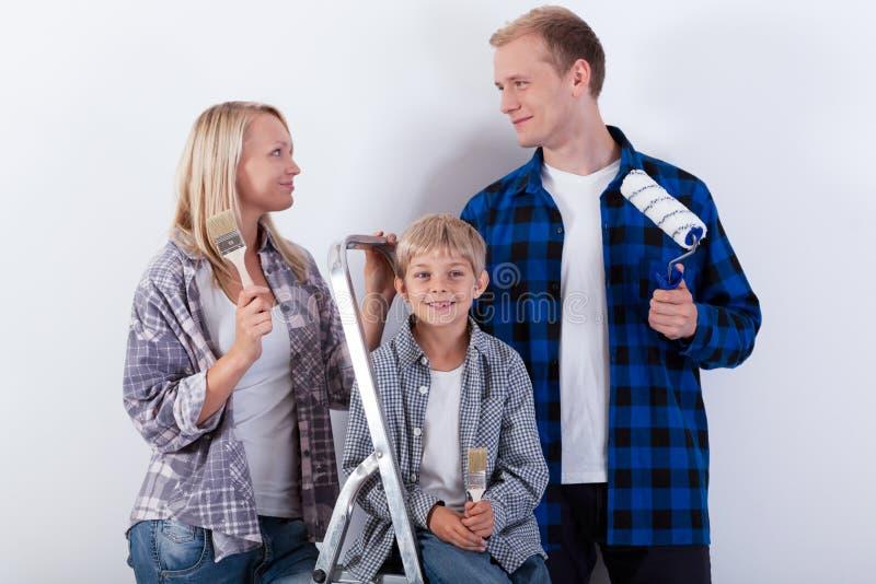 Lycklig familj som renoverar deras nya hem royaltyfri fotografi